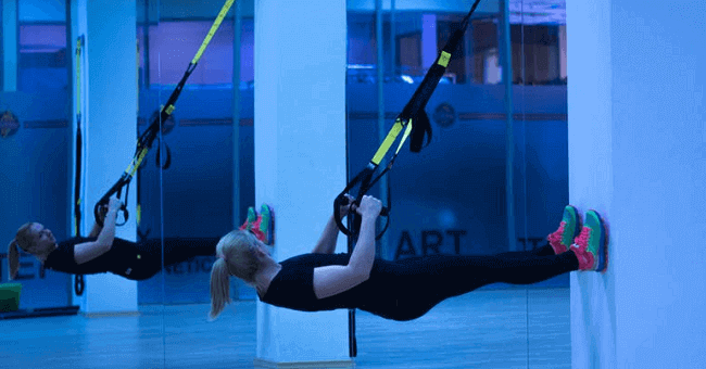 woman exercising with suspension kit