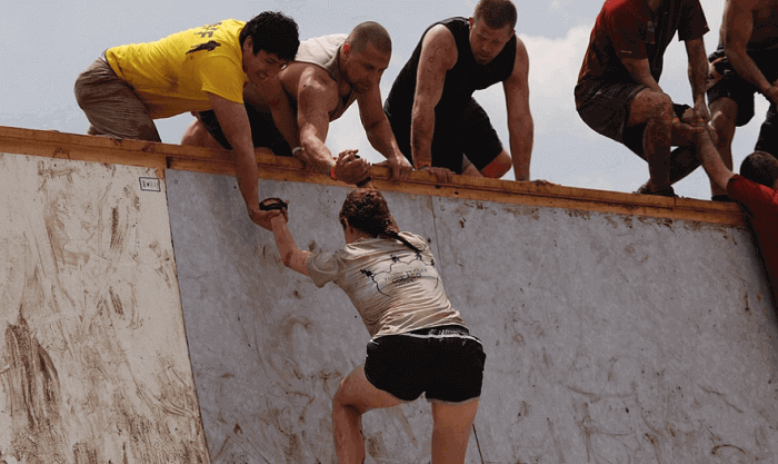 team pull teammate up a wall
